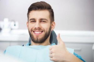 Bearded young man sitting in dental chair giving a thumbs up with a smile.