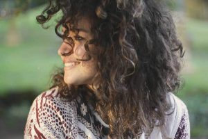 Young woman with curly hair smiling and looking to the side