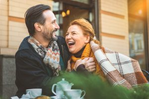 Middle aged man and woman hugging and laughing together