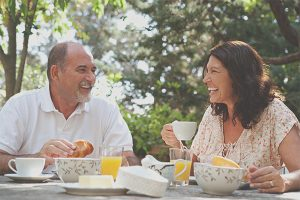 A middle aged man and woman laughing and talking while having a tea party