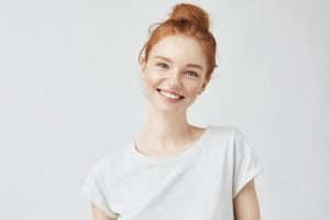 A young woman smiling in front of a white background