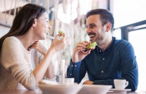 A couple smiling and laughing and eating food on a date
