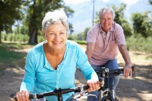 An older couple smiling and riding bikes